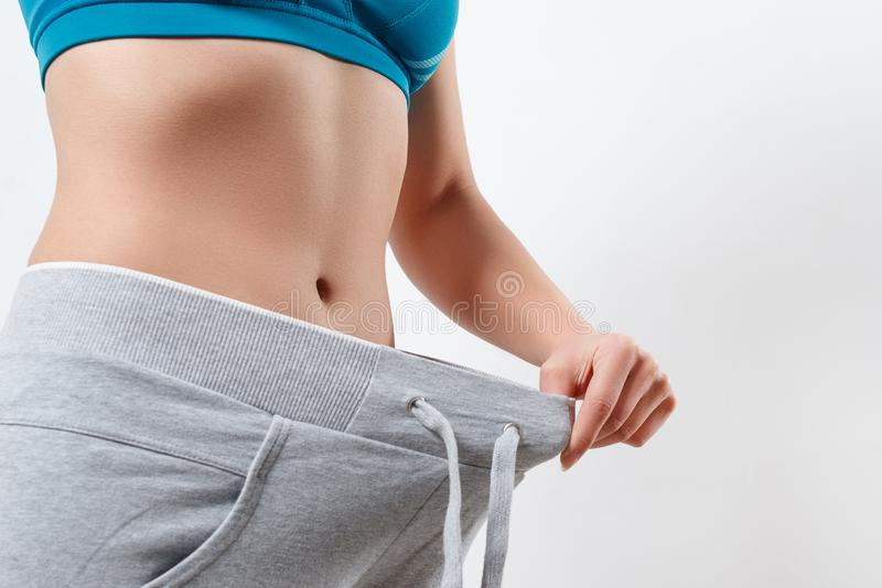 Skinny girl in big pants - weight loss concept royalty free stock image