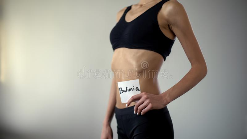 Skinny girl holding bulimia note, exhausted body needs help, eating disorder. Stock photo royalty free stock photo