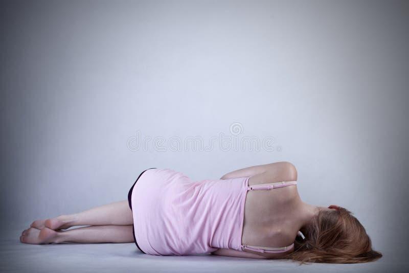 Skinny girl lying on the floor. Horizontal royalty free stock photo
