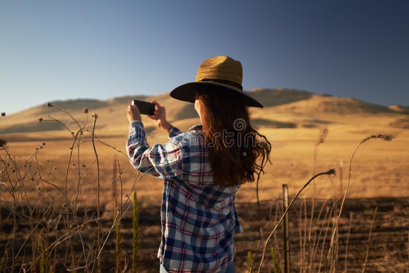 Skinny girl wearing hat taking photo of rural california landscape stock photography