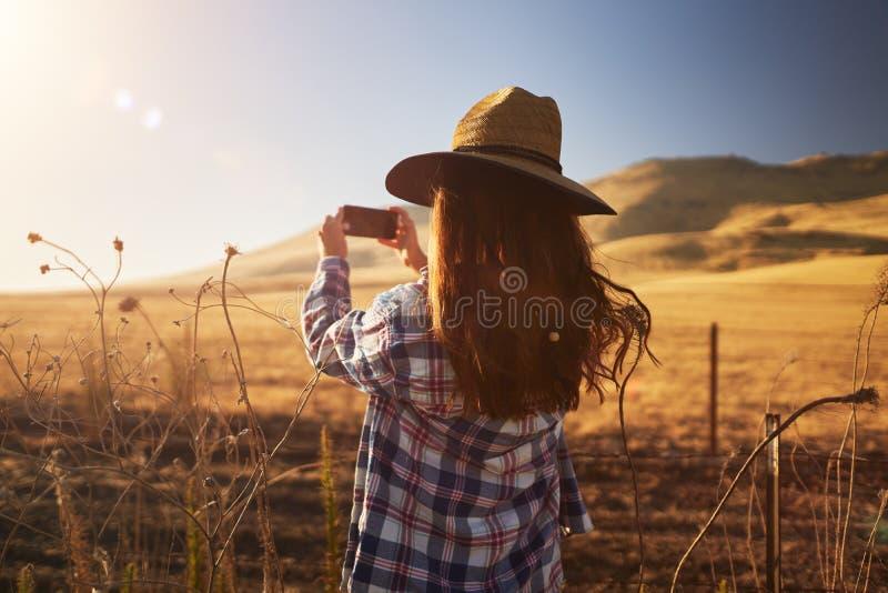 Skinny girl wearing hat taking photo of rural california landscape royalty free stock photo