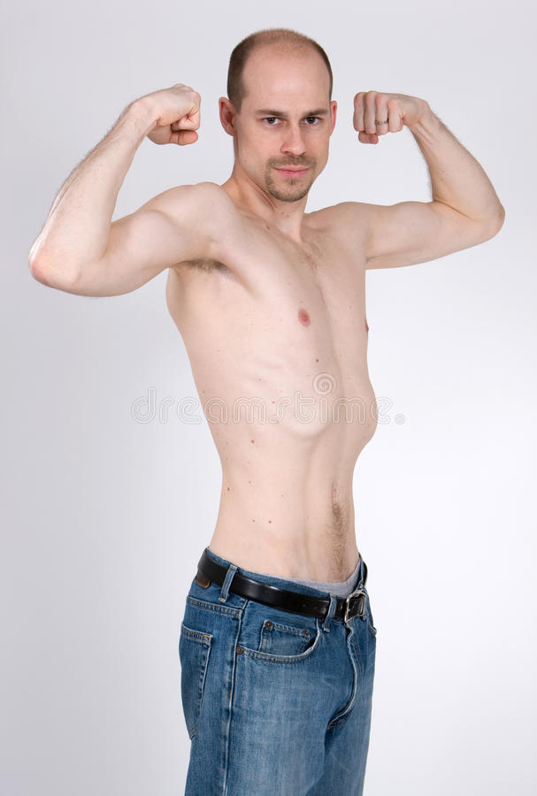 Skinny Man. A skinny man tries to pump up his muscles royalty free stock photos
