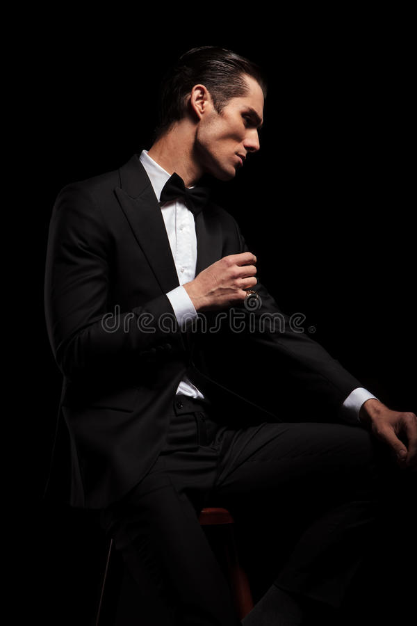 Skinny man in black with bowtie posing in dark studio. Handsome skinny man in black suit with bowtie posing seated in dark studio background while resting his royalty free stock photo