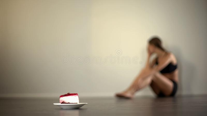 Skinny model feels nausea when looking at cake, anorexia, eating disorder. Stock photo royalty free stock photography