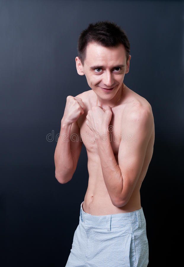 Skinny topless man. Skinny topless man showing his muscles stock images