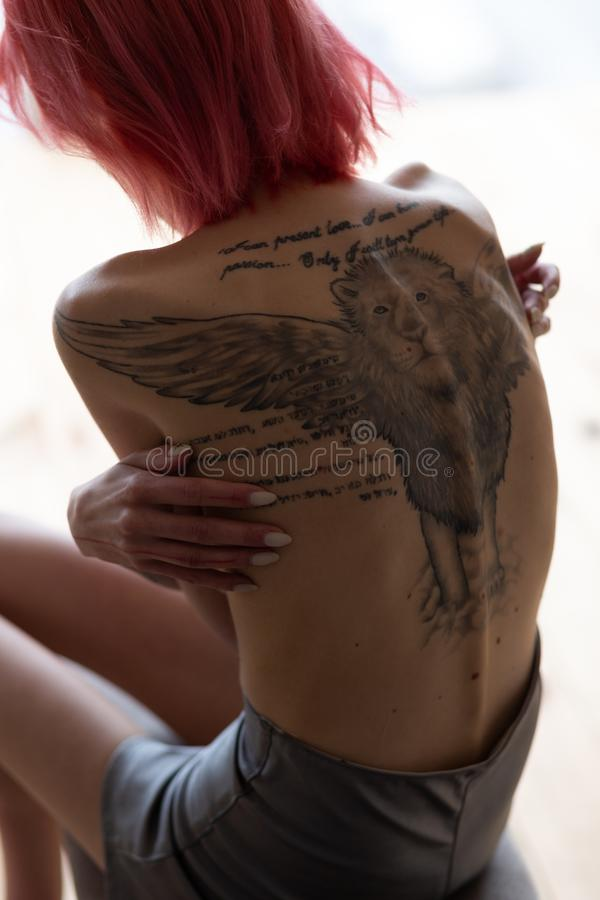 Skinny woman with anorexia showing her back with tattoo. Showing her back. Red-haired skinny unhealthy woman with anorexia showing her back with tattoo royalty free stock photos