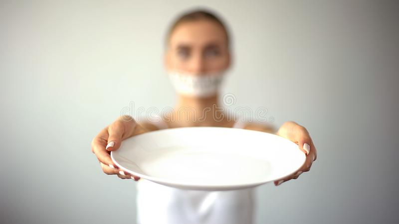 Skinny woman with taped mouth showing empty plate, concept of fasting, hunger. Stock photo stock photography