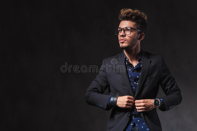 Skinny young man wearing glasses is fixing his jacket in studio. Skinny young man wearing glasses is fixing his jacket while looking up in dark studio background royalty free stock photos