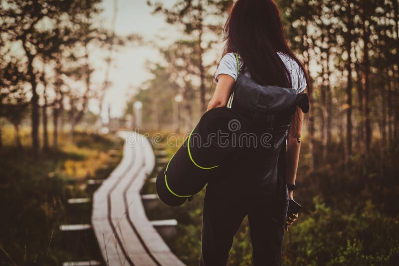 Skinny woman is hiking by the wooden path in the middle of lush pine forest. Skinny young woman is hiking by the wooden path in the middle of lush pine forest royalty free stock images