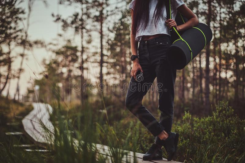 Skinny woman is hiking by the wooden path in the middle of lush pine forest. Skinny young woman is hiking by the wooden path in the middle of lush pine forest stock photo