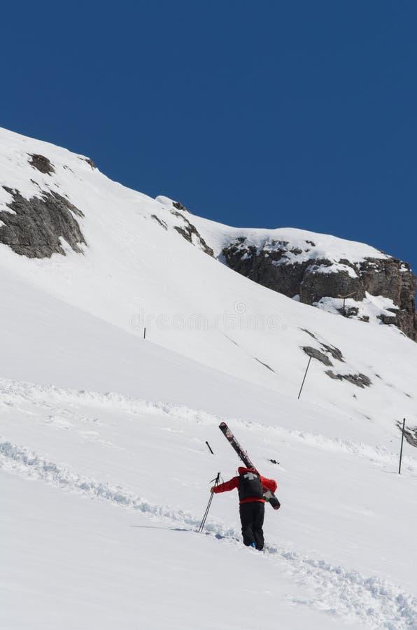 Skipatrouille, die oben einen Berghang trägt große Skis klettert lizenzfreie stockfotos