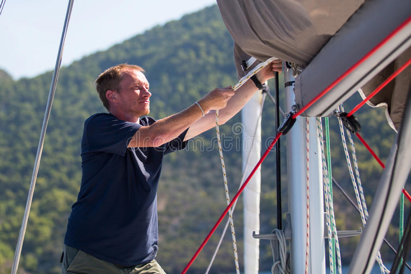 Skipper tightens the ropes on his sailing yacht. Sport. royalty free stock images