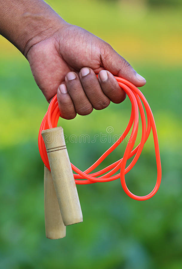 Skipping rope in hand. Hand holding a skipping rope with selective focus royalty free stock photography