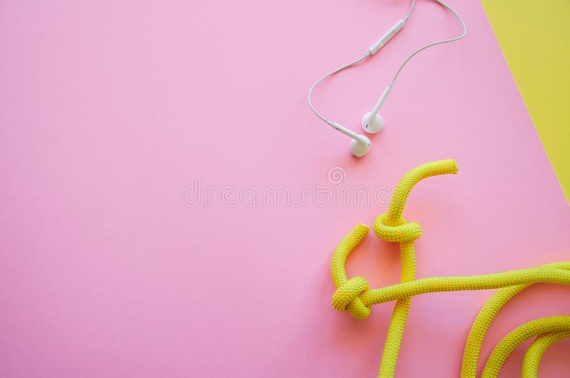 Skipping rope and headphones on a pink and yellow background. T. Op view and copy space. Sport, hobby and lifestyle concept royalty free stock photography