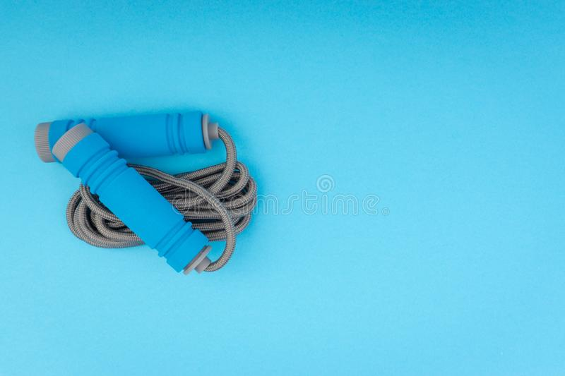 Skipping rope or jumping rope isolated on blue background. Selective focus and crop fragment stock image