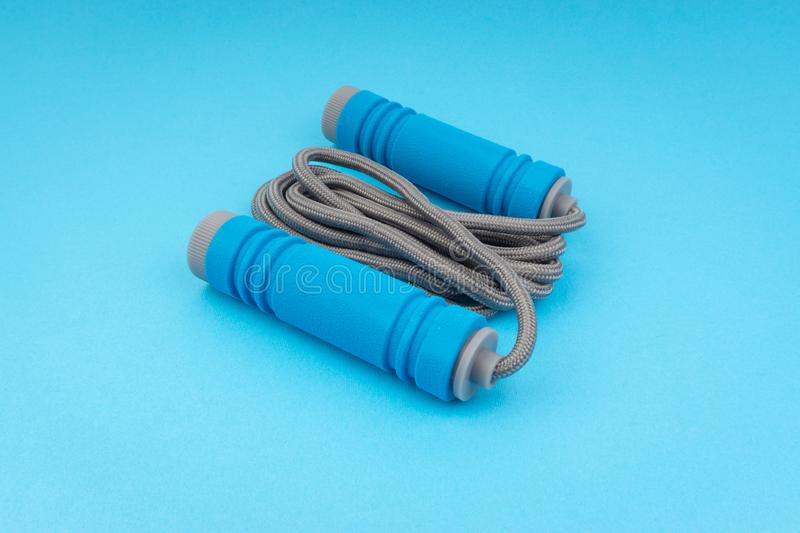 Skipping rope or jumping rope isolated on blue background. Selective focus and crop fragment stock photography