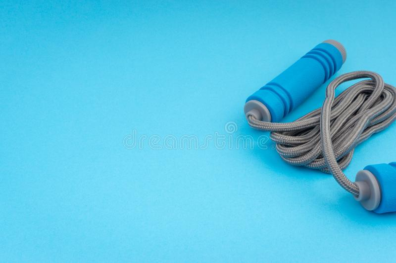 Skipping rope or jumping rope isolated on blue background. Selective focus and crop fragment stock photo