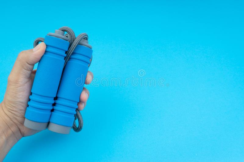 Skipping rope or jumping rope isolated on blue background. Selective focus and crop fragment stock images