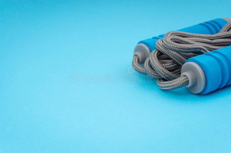 Skipping rope or jumping rope isolated on blue background. Selective focus and crop fragment royalty free stock image
