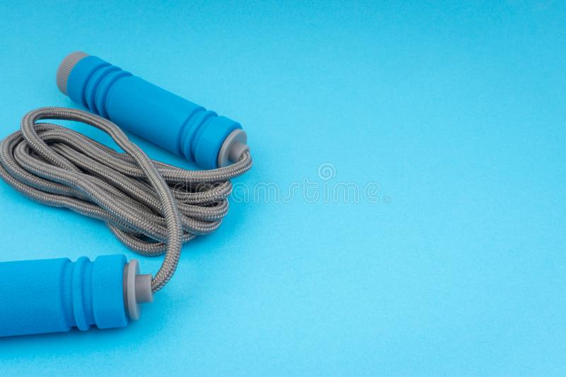 Skipping rope or jumping rope isolated on blue background. Selective focus and crop fragment royalty free stock photo