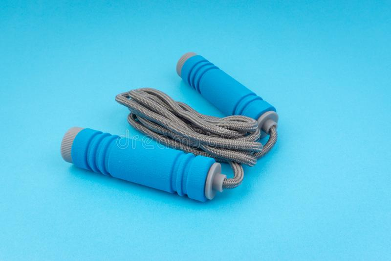 Skipping rope or jumping rope isolated on blue background. Selective focus and crop fragment royalty free stock photography