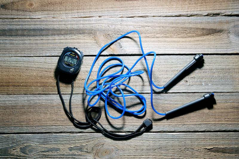 Skipping Rope and Stopwatch. On Wooden Background royalty free stock photography