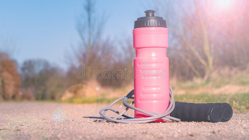 Skipping rope and water bottle on the ground outoor.  royalty free stock photo