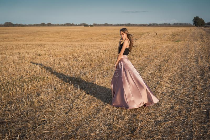 The skirt blows by the wind. Girl outside the city in the autumn field royalty free stock photo