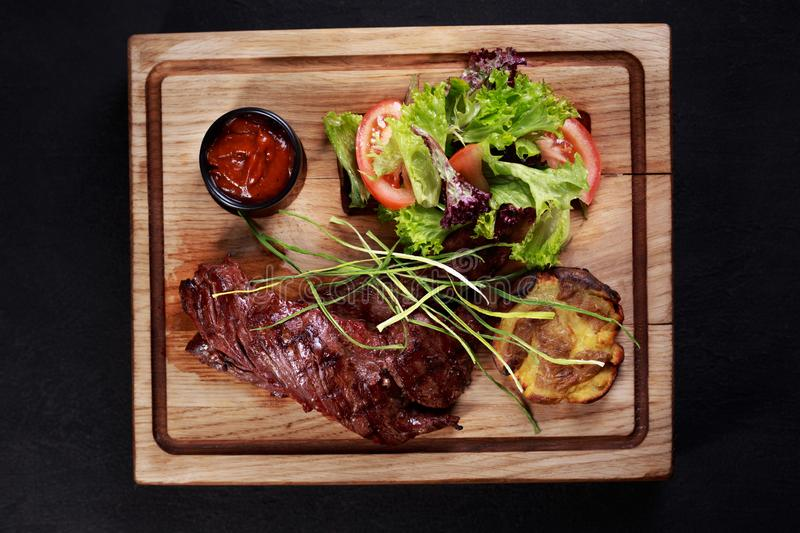 Skirt steak, grill and barbeque restaurant menu. Juicy medium rare skirt steak, meat served with vegetable salad and potatoes on board, traditional american stock photo