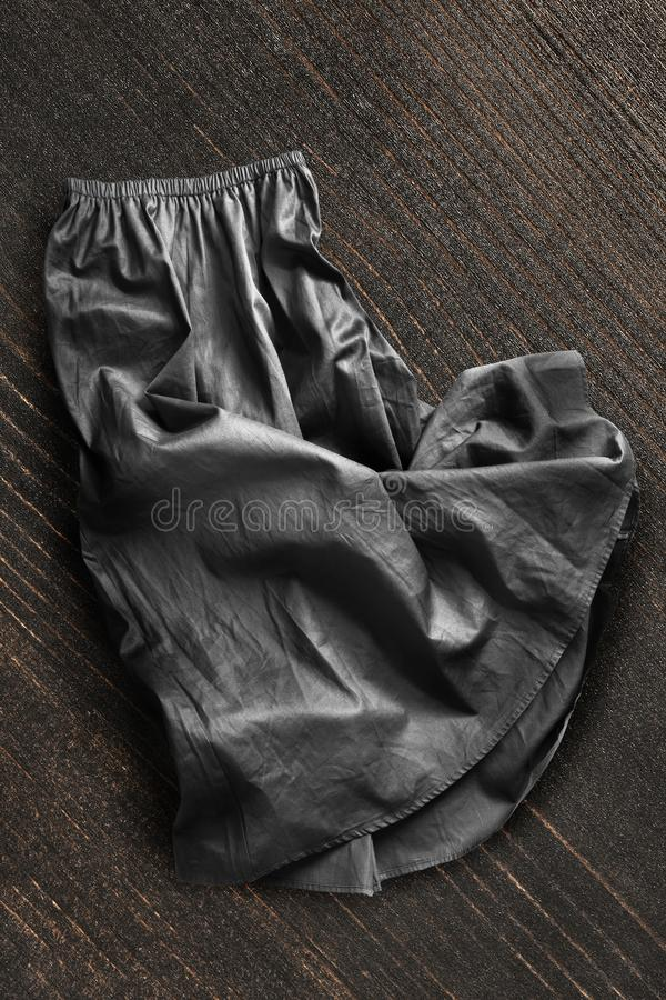 Skirt on wooden background. Crumpled black silk skirt on dark brown wooden background royalty free stock photos