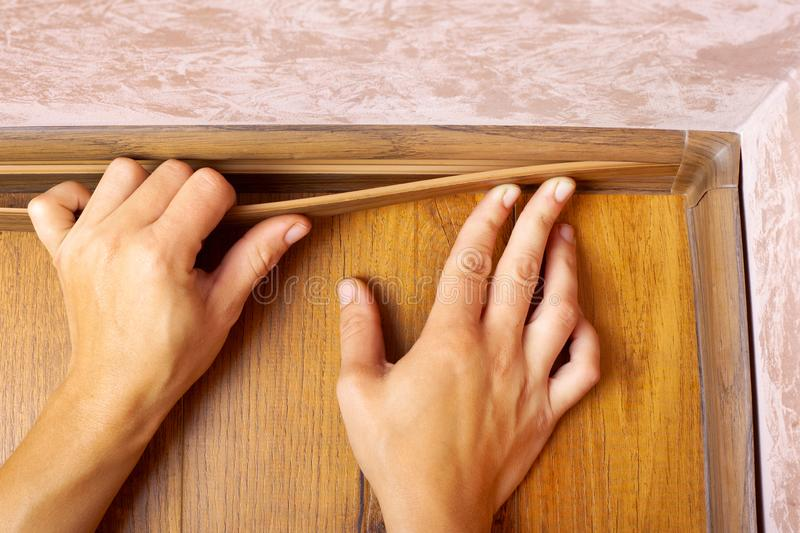 Skirting installation,master produces mounting  baseboard in the house.  royalty free stock images