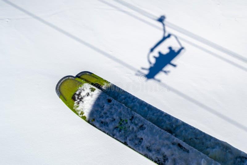 Skis boven skiërsschaduwen in stoeltjeslift boven de witte sneeuw, tijdens een vakantie van de de Winterski in Les Sybelles, Fran stock foto's