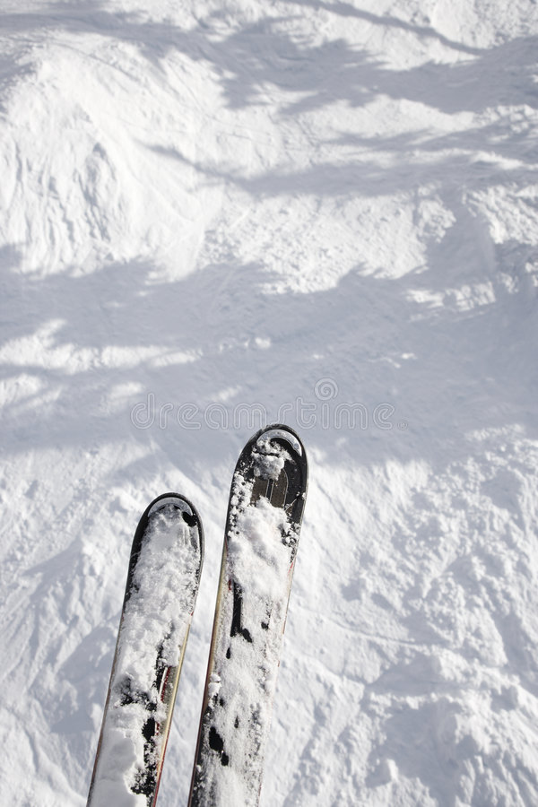 Skis dangling off trail drop stock photo