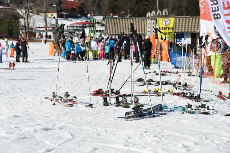 Skis and sticks on snow, people in background in alpine winter resort, apres ski on slope, Kranjska gora resort stock photos