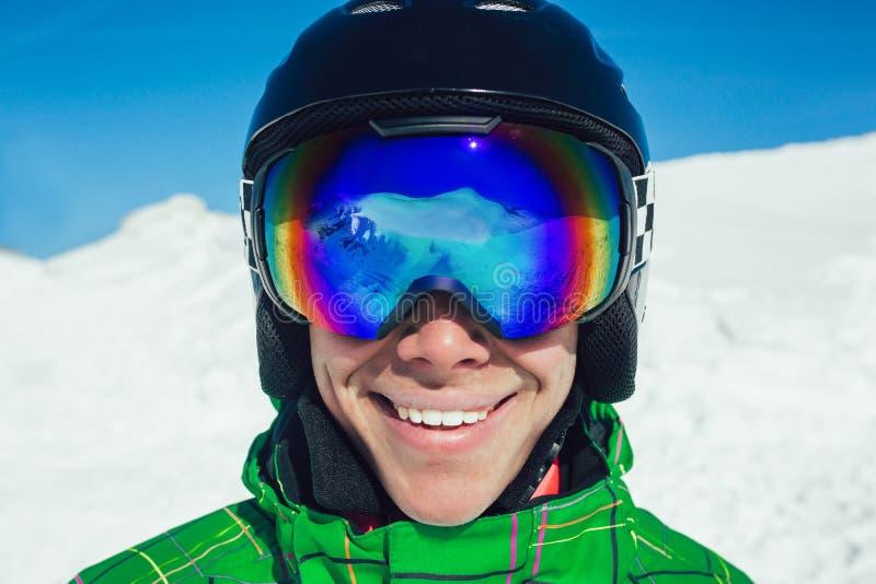 Skischutzbrillen eines Mannes mit der Reflexion von geschneiten Bergen lizenzfreie stockfotos