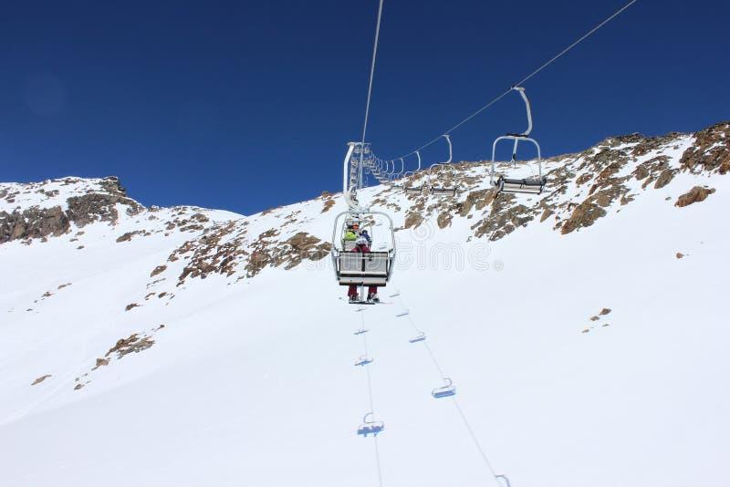 Skisesselbahn holt Leute zur Spitze des Berges stockfotos