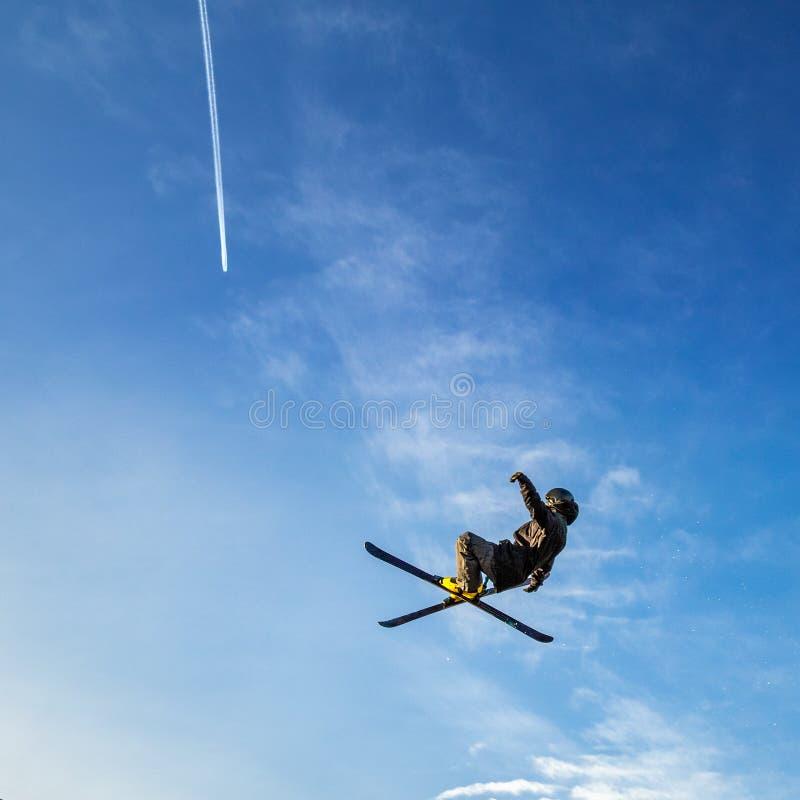 Skispringer, der hoch in die Luft auf einem Hintergrund des blauen Himmels fliegt stockbild