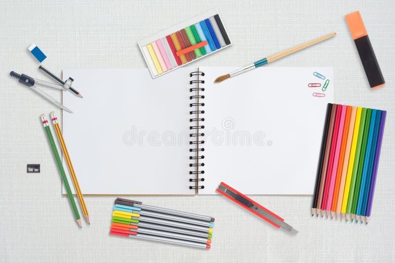Skissa bok- och målarfärghjälpmedel på tabelltorkduken för tillbaka till skolan arkivbilder