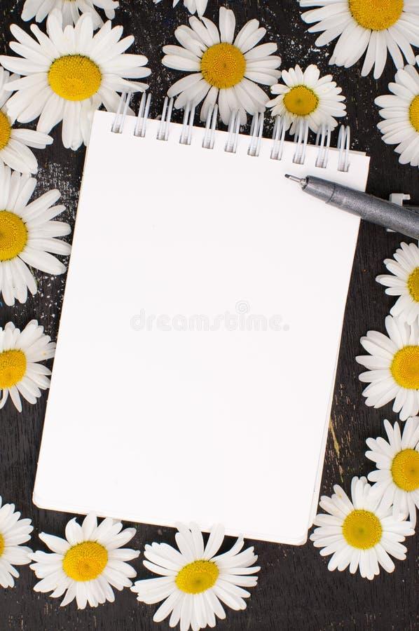 Skissa boken och skriva på en tabell som dekoreras med blommor royaltyfri bild