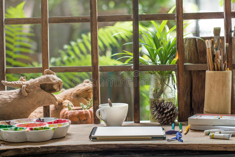 Skissa boken på konstnärarbetsskrivbordet i liten trädgård royaltyfria foton