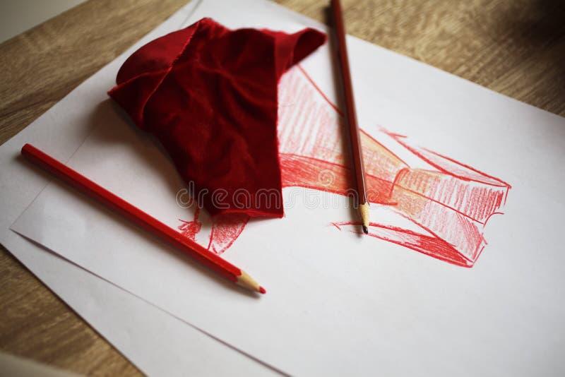 Skissa den röda klänningen som målas på vitbok och röd tygmodell royaltyfri foto