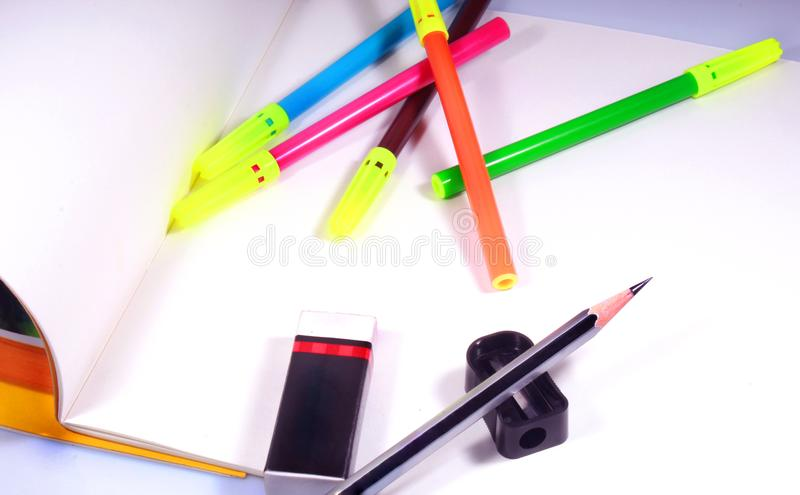Skissa pennor, blyertspennan och radergummit med den vanliga vita teckningsboken royaltyfri foto