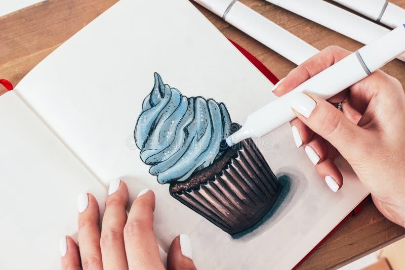 Skissa teckningen av muffin vid markörer i sketchbook med kvinnamummel royaltyfri fotografi
