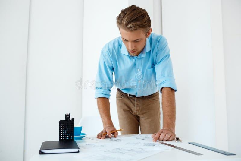 Skissar det funktionsdugliga anseendet för ung stilig säker eftertänksam affärsman på tabellteckningen Vit modern kontorsinre arkivfoton