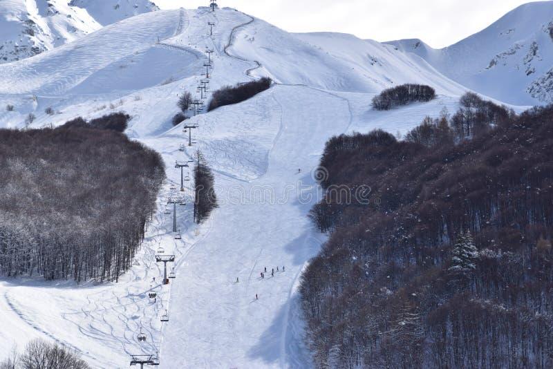 Skisteigungen und -Skifahrer stockfotos