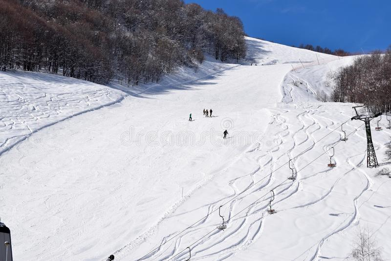 Skisteigungen und -Skifahrer stockfoto