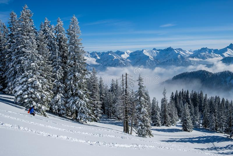 Skitouring在奥伯斯特多夫附近的Allgaeu阿尔卑斯在一美好的蓝鸫天在冬天 免版税库存图片