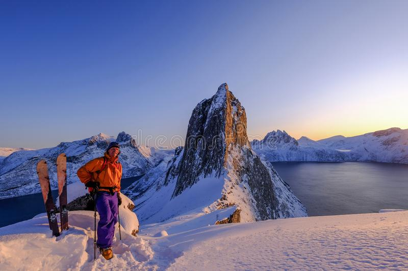 Skitouring man standing at the ridge in front of the iconic Segla mountain, view of the ocean fjords, Fjordgard, Norway. Skitouring man standing at the ridge in royalty free stock image