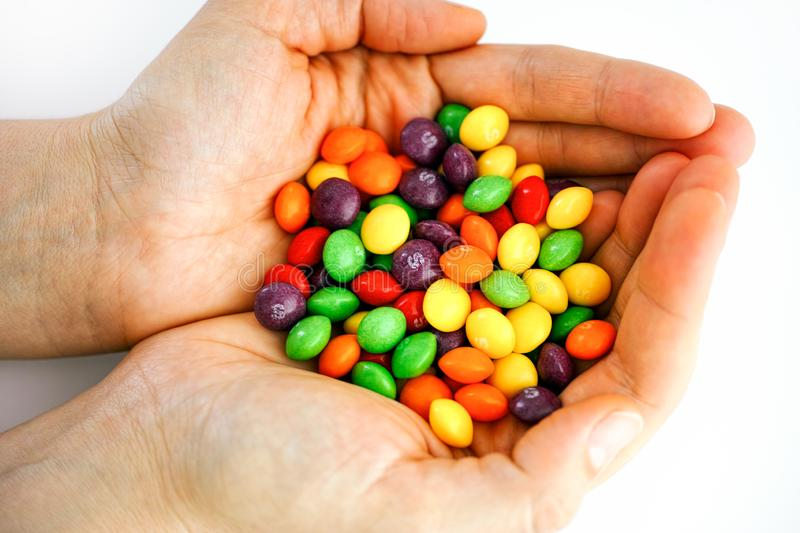 Skittles multicolored fruit candies in woman hands. Tambov, Russian Federation - December 05, 2019 Skittles multicolored fruit candies in woman hands. White stock photography