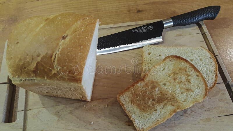 Skiva av bröd på ett gammalt träbräde med en svart kniv arkivfoton